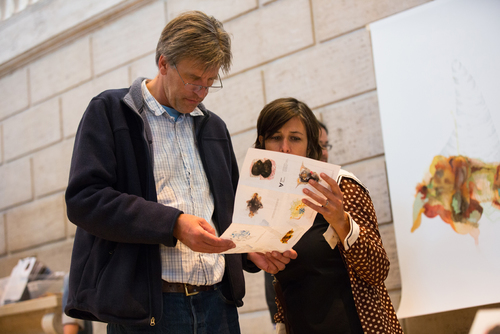 Museum visitors examine   Re:depiction   map to locate original artworks as described by museum staff.