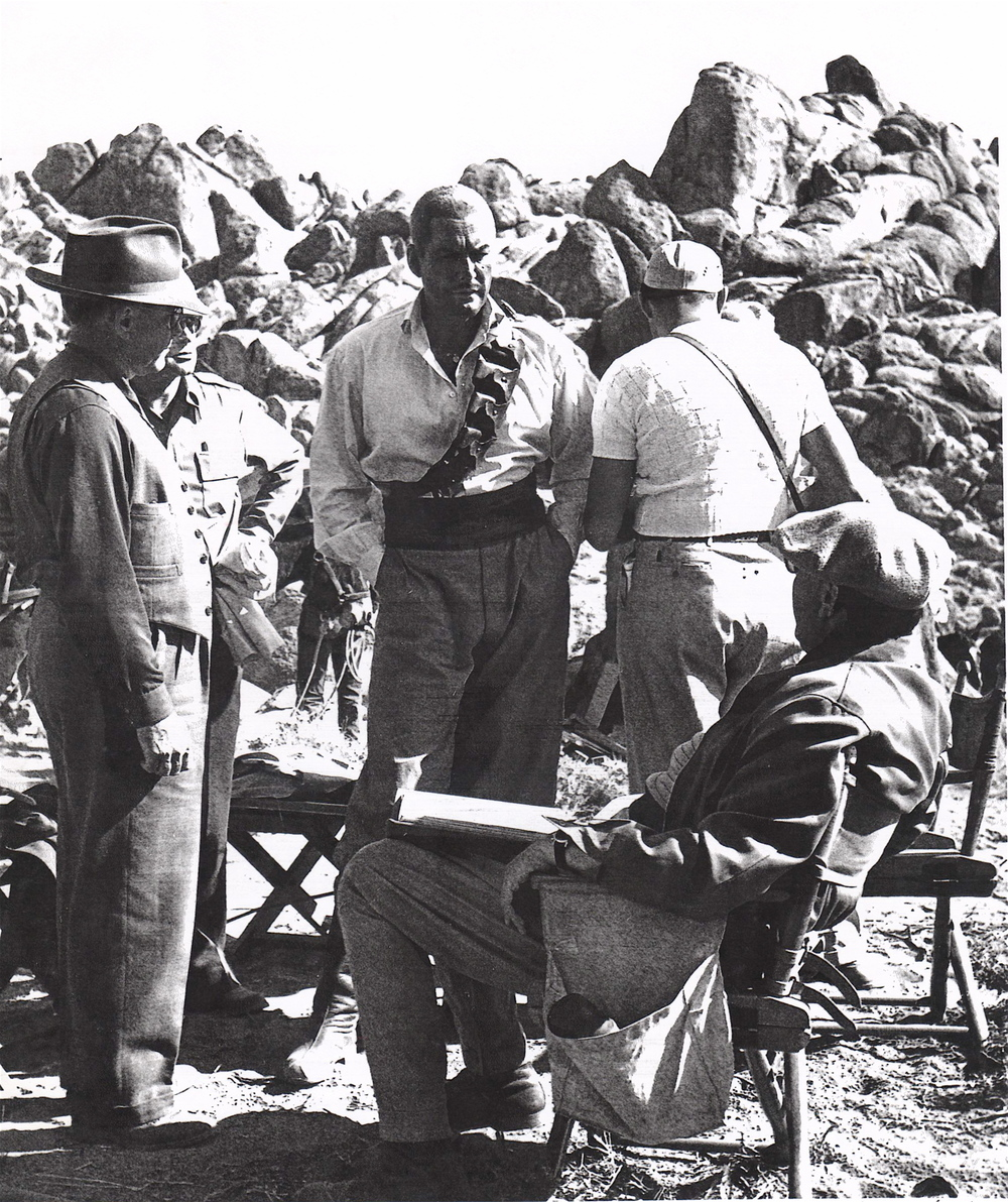 Director Victor Saville (sitting) instructs his star Errol Flynn exactly what he wants for Red Beard.
