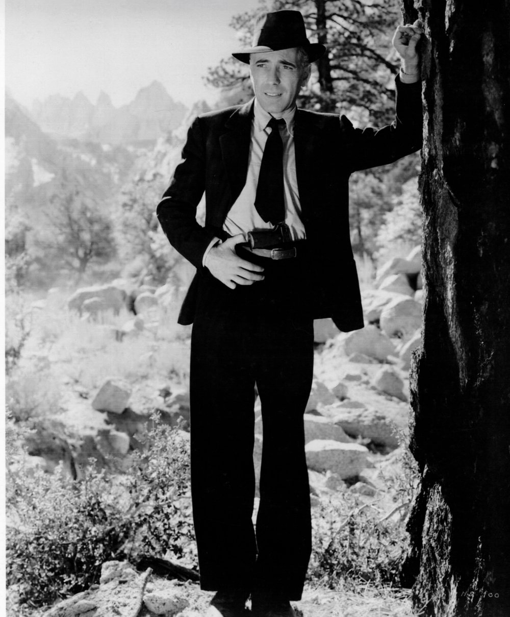 Humphrey Bogart stands in his iconic pose as Roy Earle on the cliffs in front of Mt. Whitney.