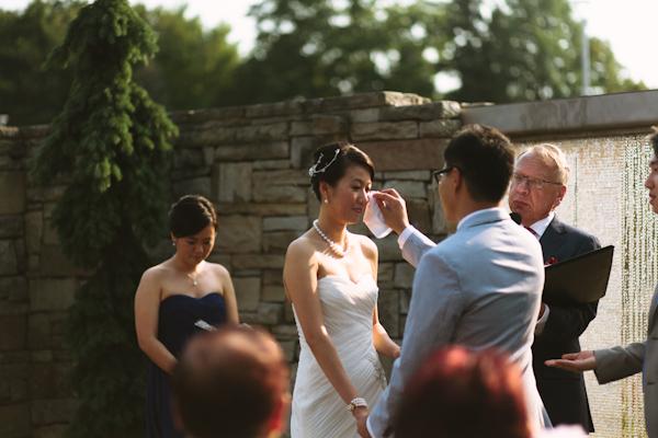 groom wiping bride's tears away at wedding ceremony
