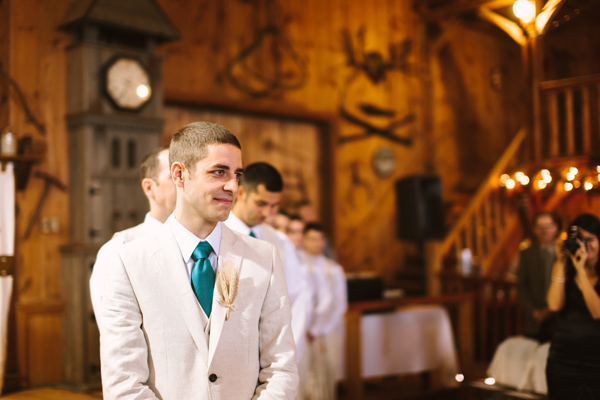 groom watches bride come down aisle at barn wedding