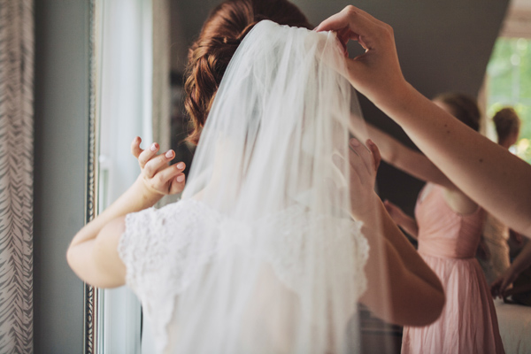 bride puts on veil before wedding