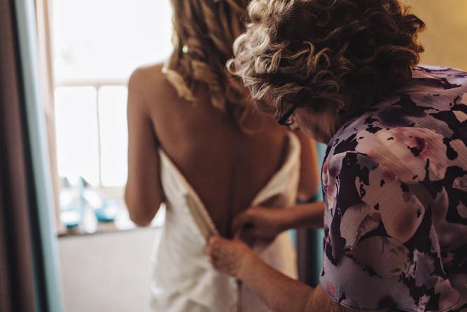 mom helps daughter into wedding dress
