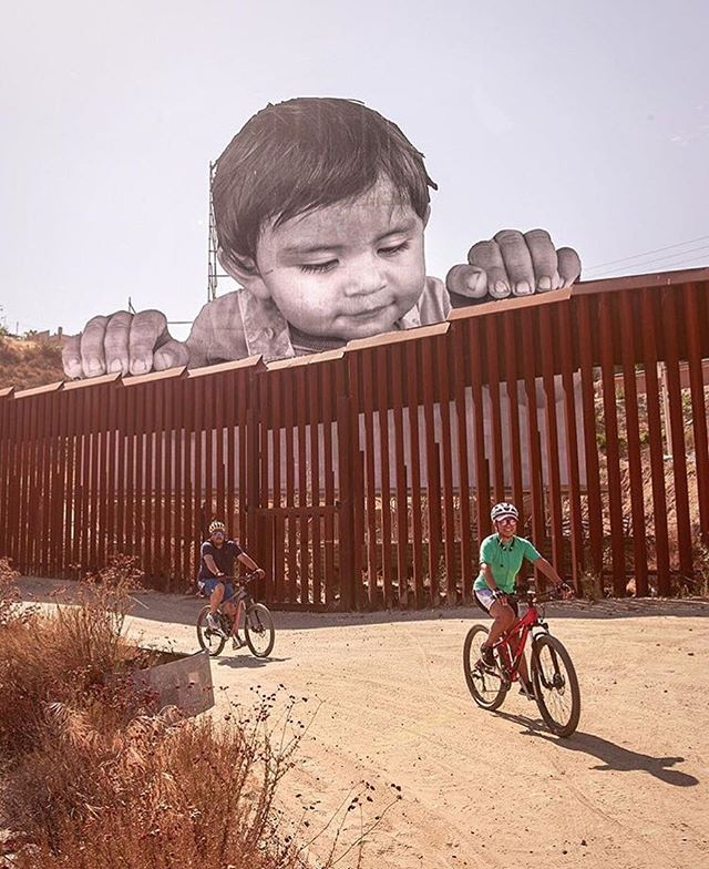"""An amazing new piece of public art installed by French Artist, @jr on the in Tecate, Mexico. This photo of a 1-year-old boy is only viewable from the American side of the fence. """"When we built walls, people built tunnels. When we closed places, they went by the water. The history of humanity is the story of people migrating."""" . . . . #JR #Art #publicart #mural #artinstallation #mexico #immigration #streetart #photography #photographer"""