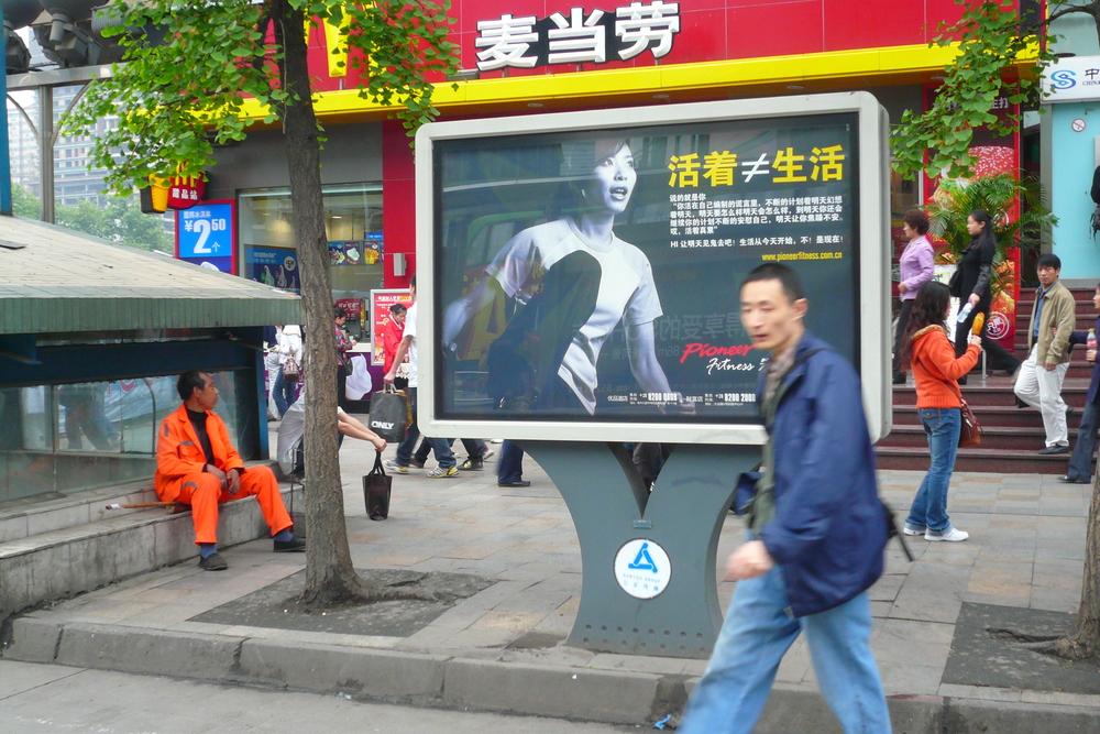 """Gestiegene Erwartungen im Sinne von """"Am Leben sein und erfüllt leben ist nicht das selbe"""". Einkaufsmeile in Chengdu. Im Hintergrund Mc Donalds."""