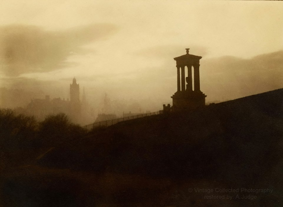 This wonderfully atmospheric photo is taken from the private collection of Alan Judge (again!). It shows Auld Reekie when it was really, ehm, reekie! Here, the photographer is standing behind the Dugald Stewart Memorial at evening time, looking along Princes Street towards the West End. The castle is only just visible on the horizon and we are also able to make out the North British Hotel and the spire of St John's Church as well as many rooves and chimney pots. The photographer is unnknown and any suggestions would be welcome.  The monument itself was designed by William Henry Playfair and was built in 1831 as a memorial to the philosopher whose name it carries. He held the chair in Moral Philosophy at Edinburgh University from 1786 until his death.  Those who see a resemblance between this and the nearby Burns Monument may be interested to know that they were actually both based on the Choragic Monument of Lysicrates in Athens. Both of these monuments, together with our infamous Edinburgh's Disgrace ( or National Monument ) truly are a homage to our city being the Athens of the North!  With many thanks again to Alan for allowing us to use this image which highlights the beauty of our city's buildings and which we here at Scott & Brown have prided ourselves on maintaining, restoring and preserving since 1890. Please take a look at his Facebook page,   https://www.facebook.com/groups/1456193791357819/?ref=nf_target&fref=nf  , to enjoy more of his wonderful images from the past which he lovingly and magically restores. Photograph copyright Alan Judge, Vintage Collected Photography.