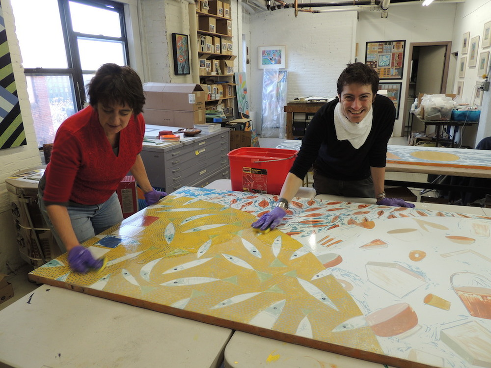 Rika Smith McNally and Rory Beerits of the Cambridge Arts Council, cleaning the mural to prepare the surface for painting with Golden acrylics.
