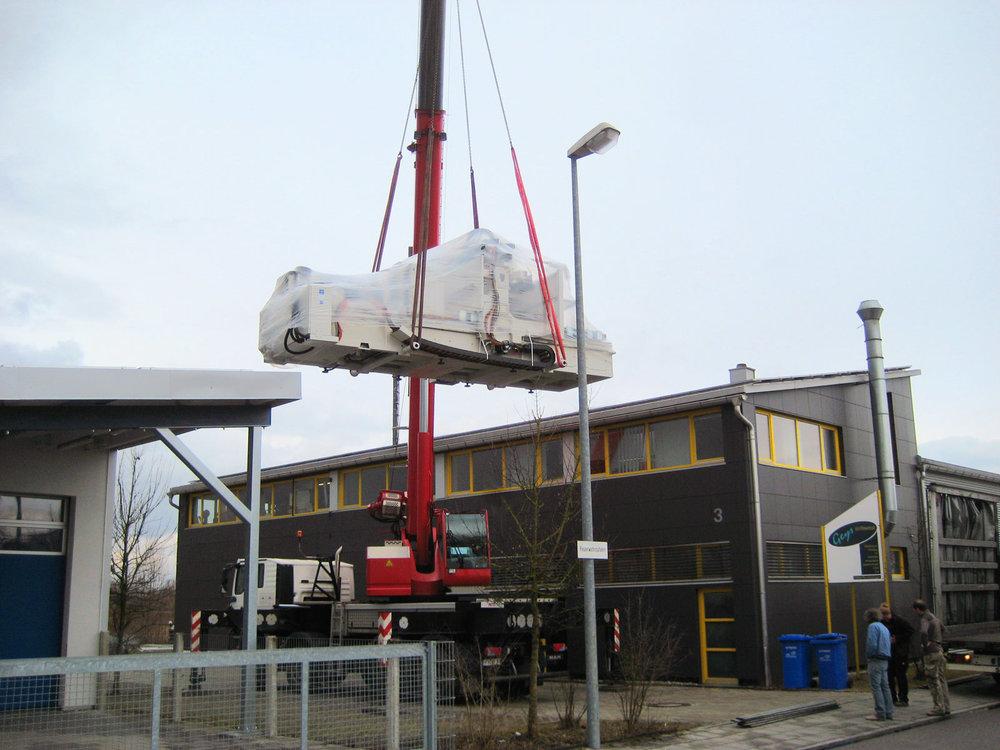 Mit einem Lastenkran wurde 2007 die neue 5-Achs-CNC-Fräse in die Möbelwerkstatt Geys gehoben.