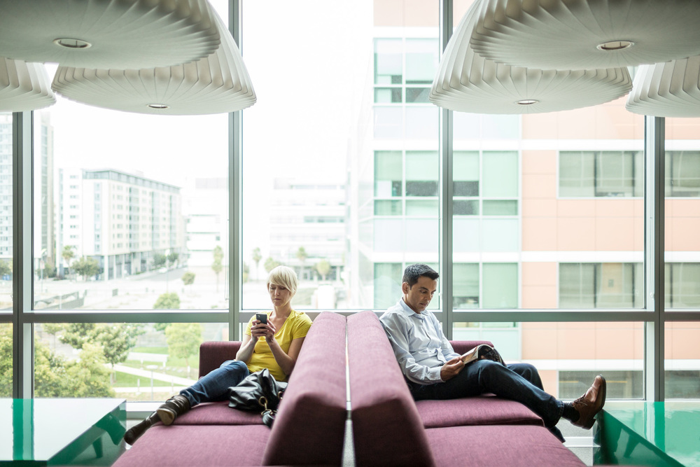casual man and woman reading and texting on a cellphone or mobile device in an office lounge