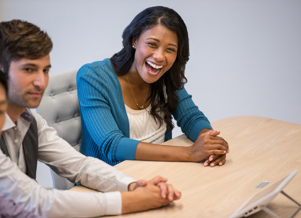 Young diverse african american woman laughing in a modern business teleconference meeting