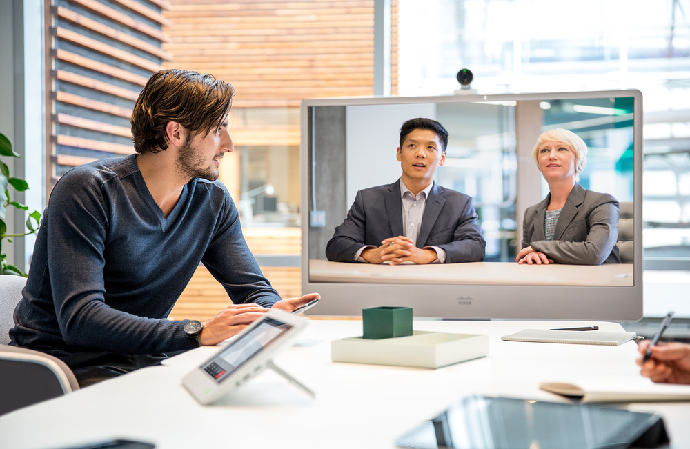 Man collaborating with ethnic male and executive woman using cisco telepresence in a modern building