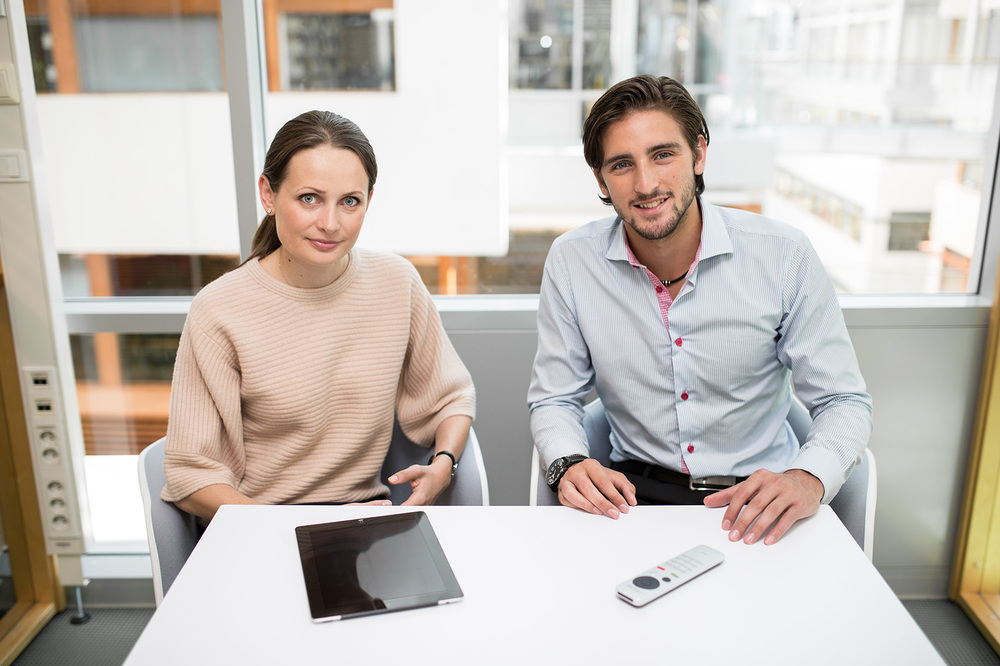 fashionable younger man and woman at work with a remote control and a tablet