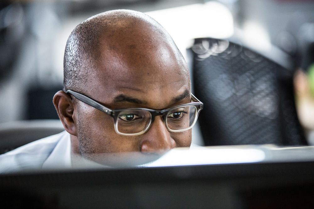 smart dressed African American man at tech company hard at work