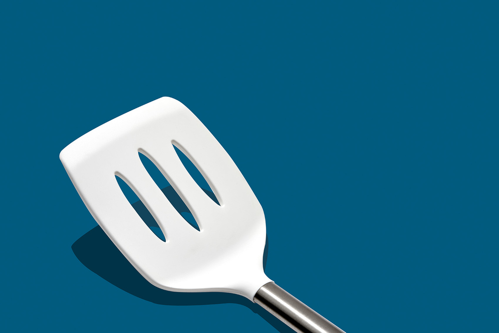 beautiful modern still life of spatula kitchen utensil on blue background