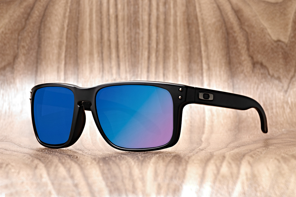 oakley sunglasses with colorful lenses on wood background
