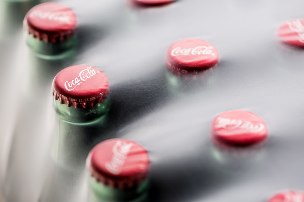Coca Cola soda bottles close up under plastic wrap packaging