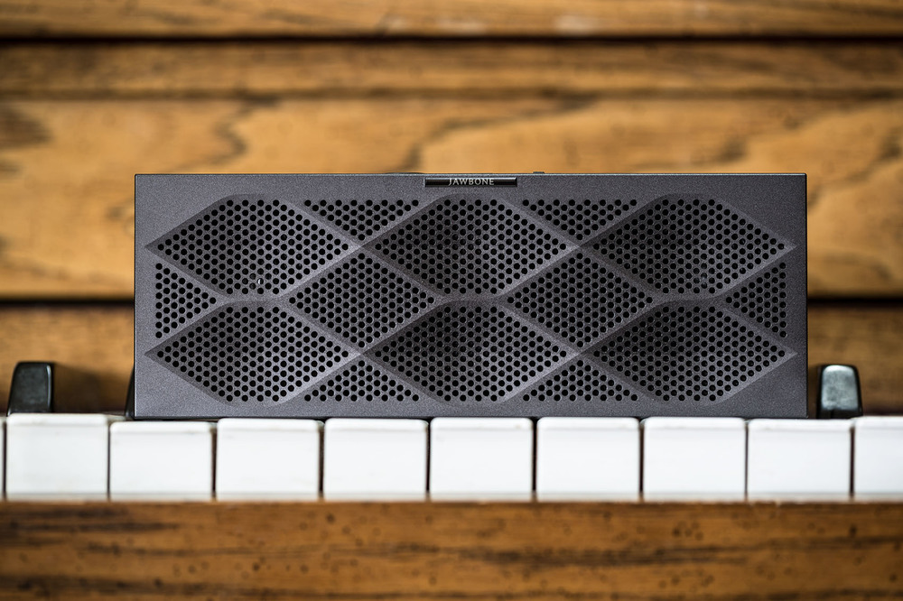 Bluetooth jawbone wireless speaker on a wood piano