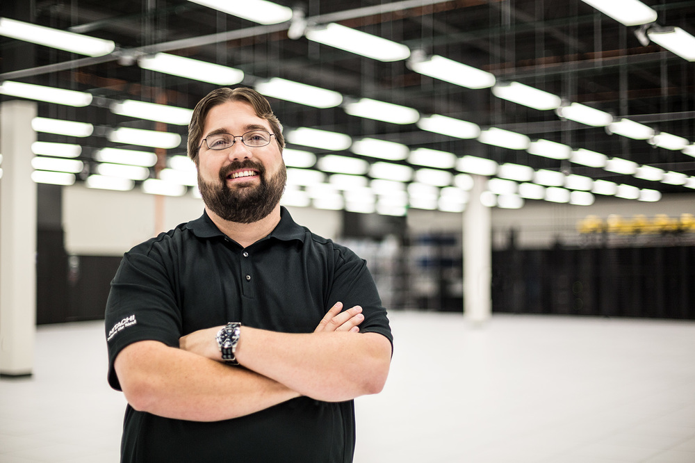 bearded engineer in data center warehouse with arms crossed