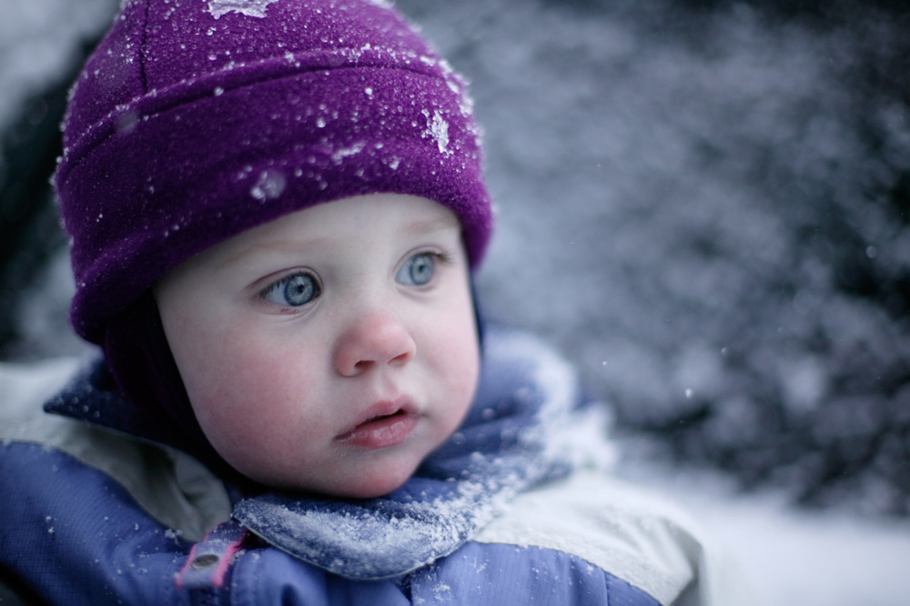 toddler girl portrait in winter snow clothing during snowfall