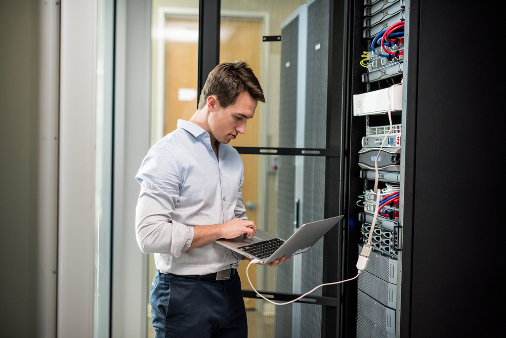 Young man working on computer in a data center