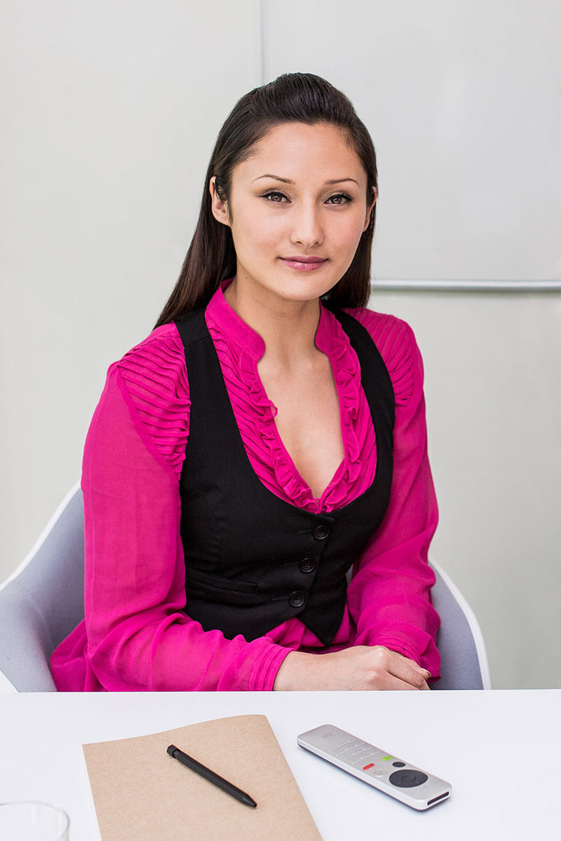 Ethnic young business woman in modern office conference room teleconferencing