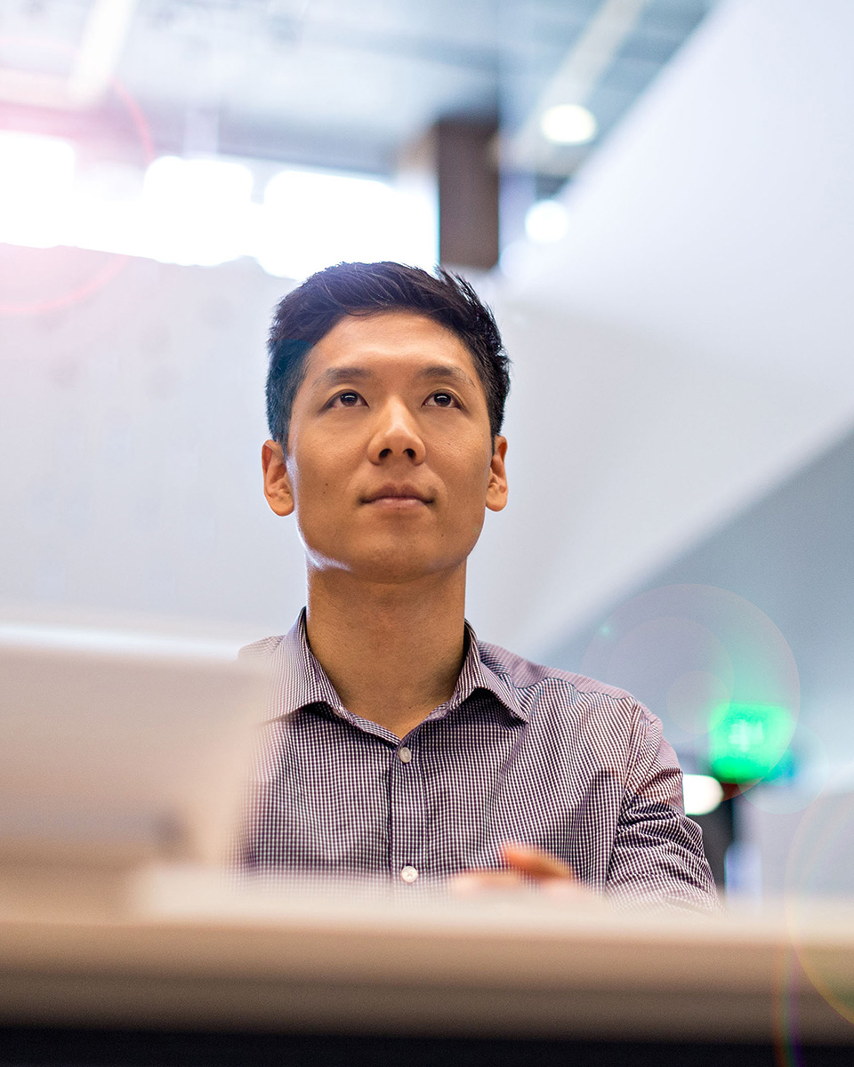 Young Asian man in silicon valley using virtual meeting software with tablet computer on desk