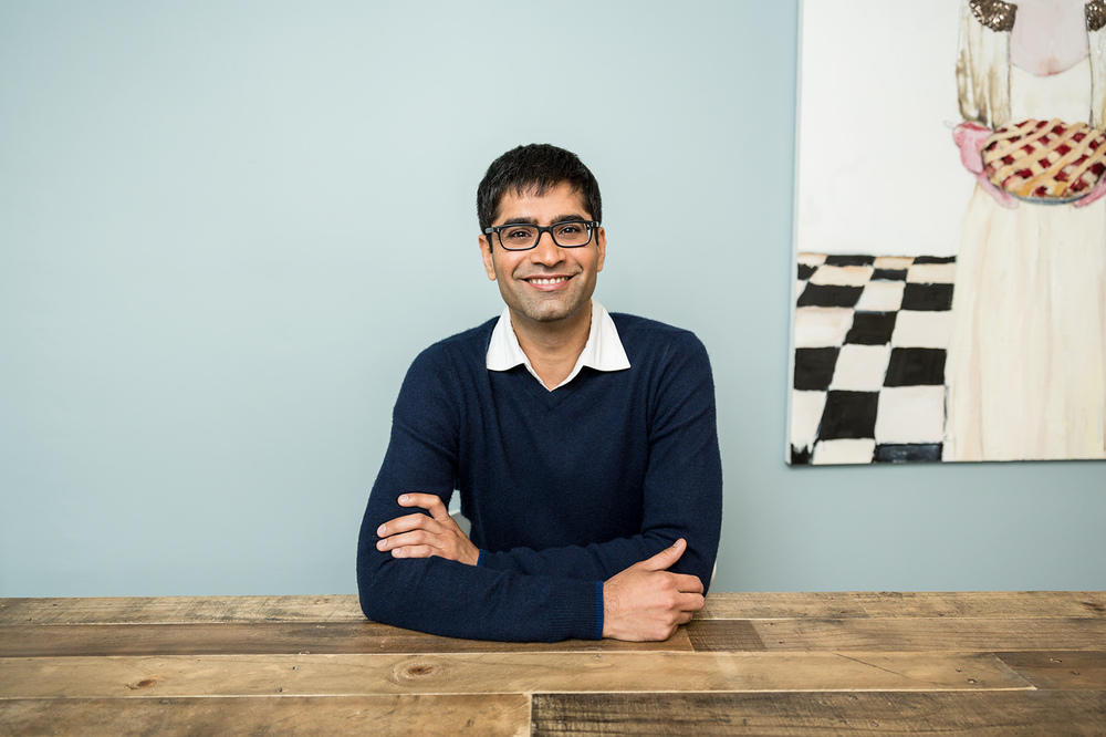 Ethnically diverse young man in glasses sitting at a wooden table at home
