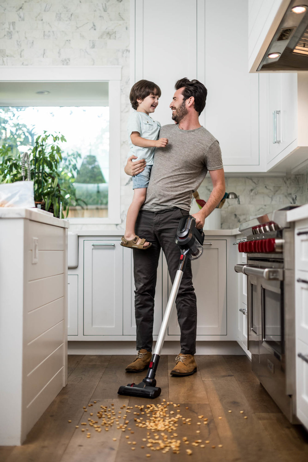 Man holding a child while vacuuming a kitchen