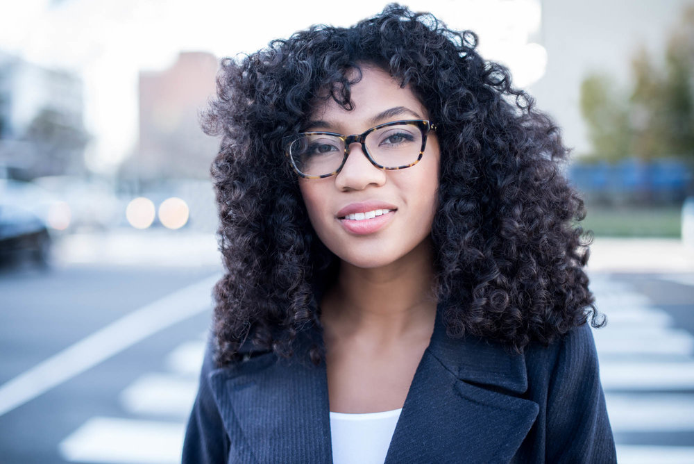 Young african american woman in glasses in a city
