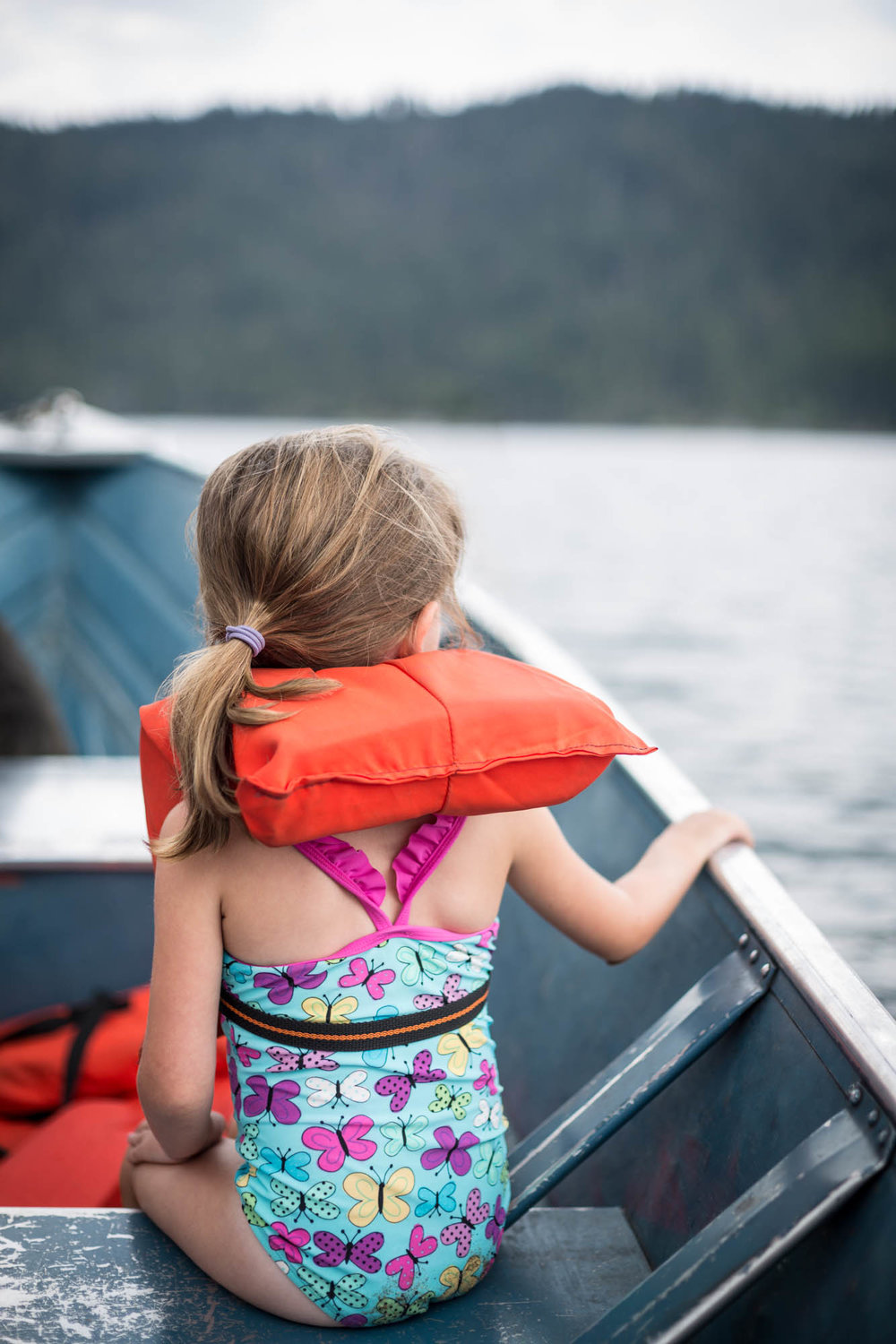 Young girl wearing a life vest on a small boat