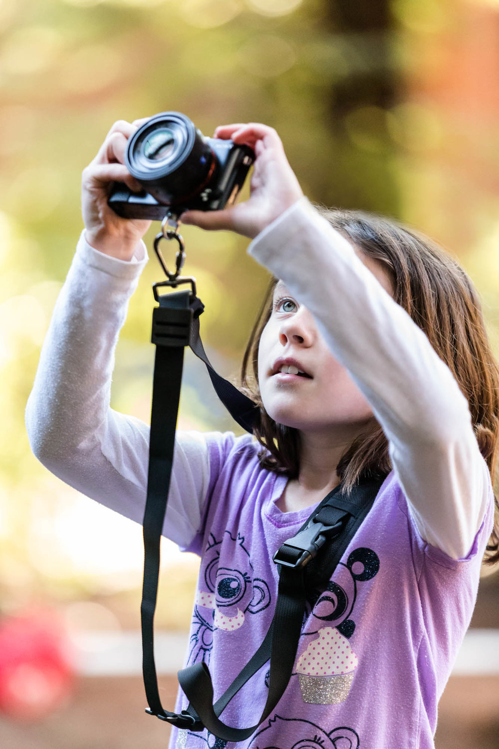 young girl taking a photo with a camera