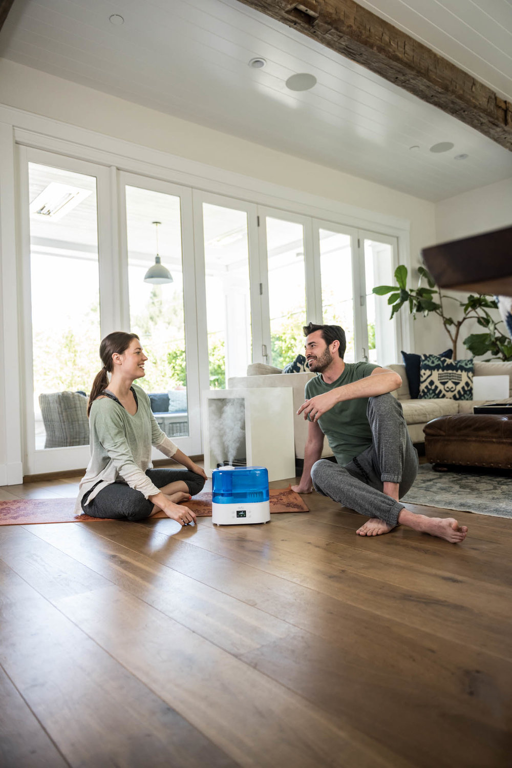 Young couple talking on the floor with a humidifier