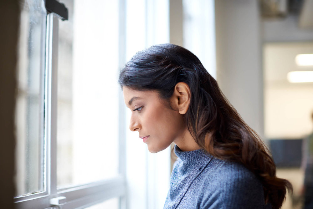 Young indian woman looking out of a window in an office
