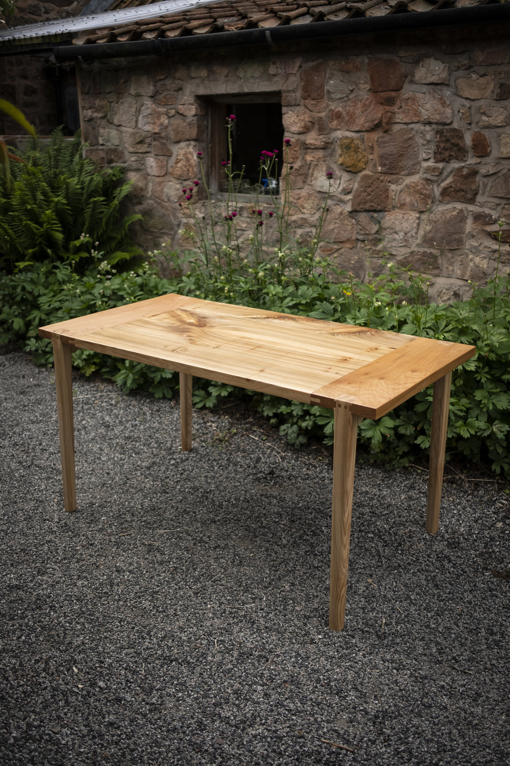 Edesia Table - This Wych Elm and Olive Ash dining table seats 6 around the rectangular figured top. Featuring sturdy and beautiful Maloof (rabbet and tenon) joints and hand shaped Ash stretchers, it is sturdy enough for a feast.