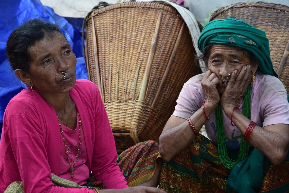 BARAM AND GURUNG DIDI   They come from Thumi, a village set very high in the mountains. They are from same village and are best friends always looking out for each other. Their village was completely destroyed during the earthquake by a landslide. About 700 people became homeless that day and they formed a camp to live in at a nearby forest. There was very limited access to water (the landslide had destroyed the village's water source); the nearest access was one-and-a-half hour walk away (one way).  Both Didis come from the family of stone workers who made handmade roofs. They learned this work from their fathers at seven and eight years old and continue teaching younger generations.. They never went to school. They are able to construct houses from stones.  I met them during the earthquake and they said that they will be able to rebuild their house. They were sad that since the landslide made the path impassible and they weren't able to get back to what is left of their homes to look for their belongings. All their food storage (rice, lentils, corn) was covered by the landslide. The whole village was left with nothing to eat.  We were able to organize aid for their village.