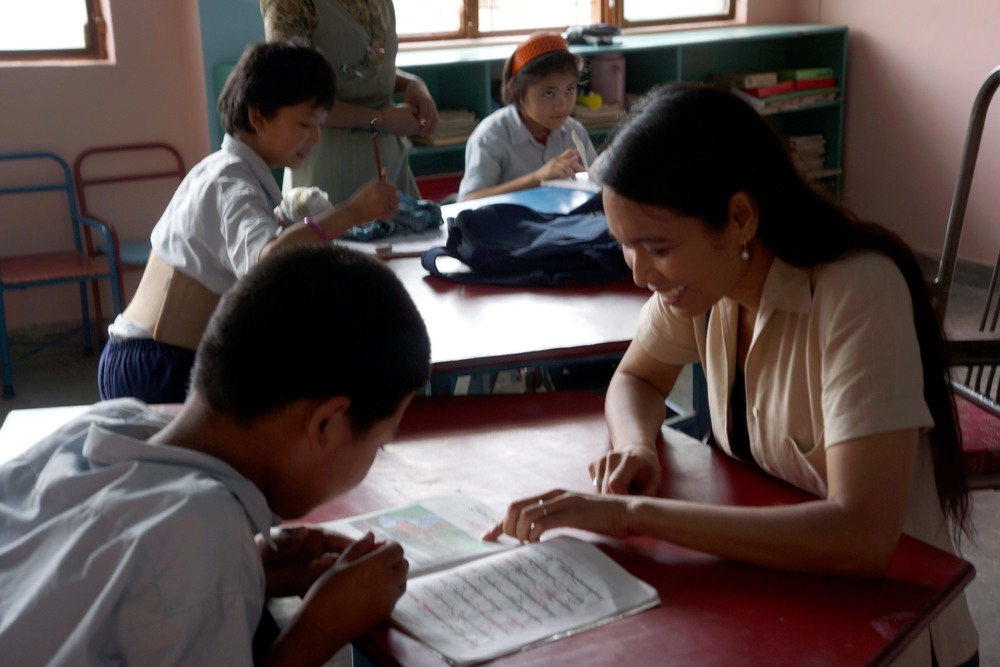 Ana Rowena McCullough sits across from a Tibetan boy, mentoring him