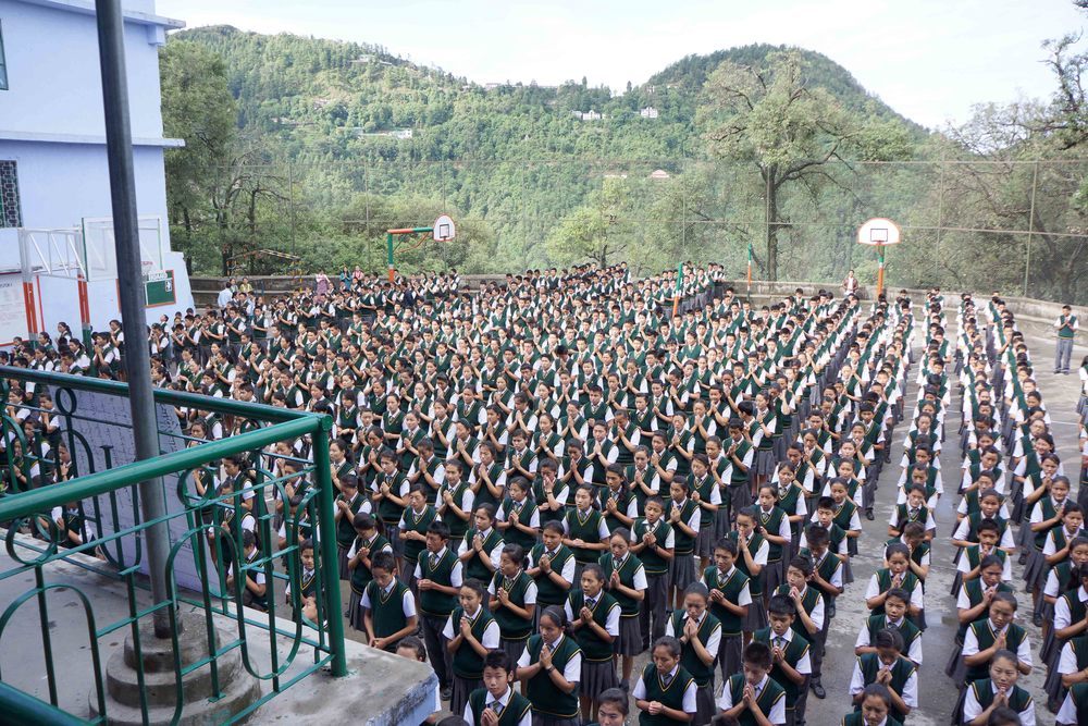 Tibetan students sitting in an assembly outdoors