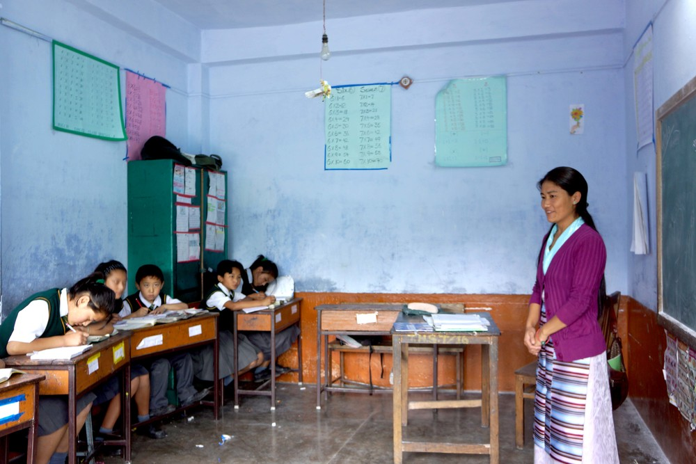 Tibetan schoolteacher (right) watches over a group of students working on the left