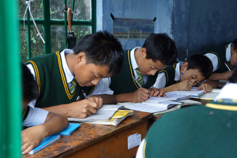 Tibetan schoolboys working with their heads down