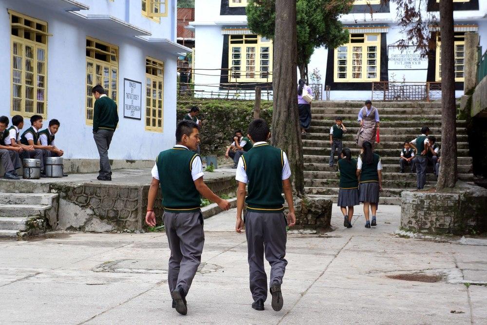 Tibetan students walk in a courtyard outside