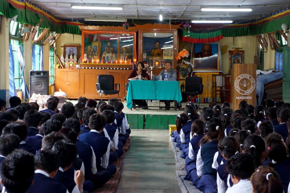 Tibetan students sitting quietly at an assembly as they listen to speakers