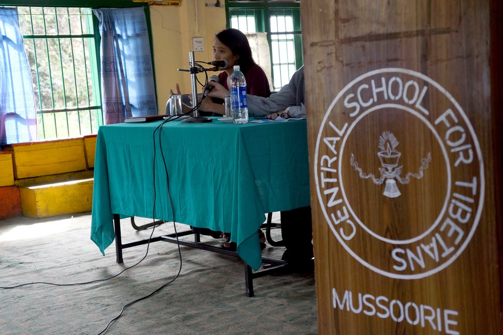 """Two presenters give a talk. Next to them is a podium that reads """"Central School For Tibetans, Mussoorie"""""""