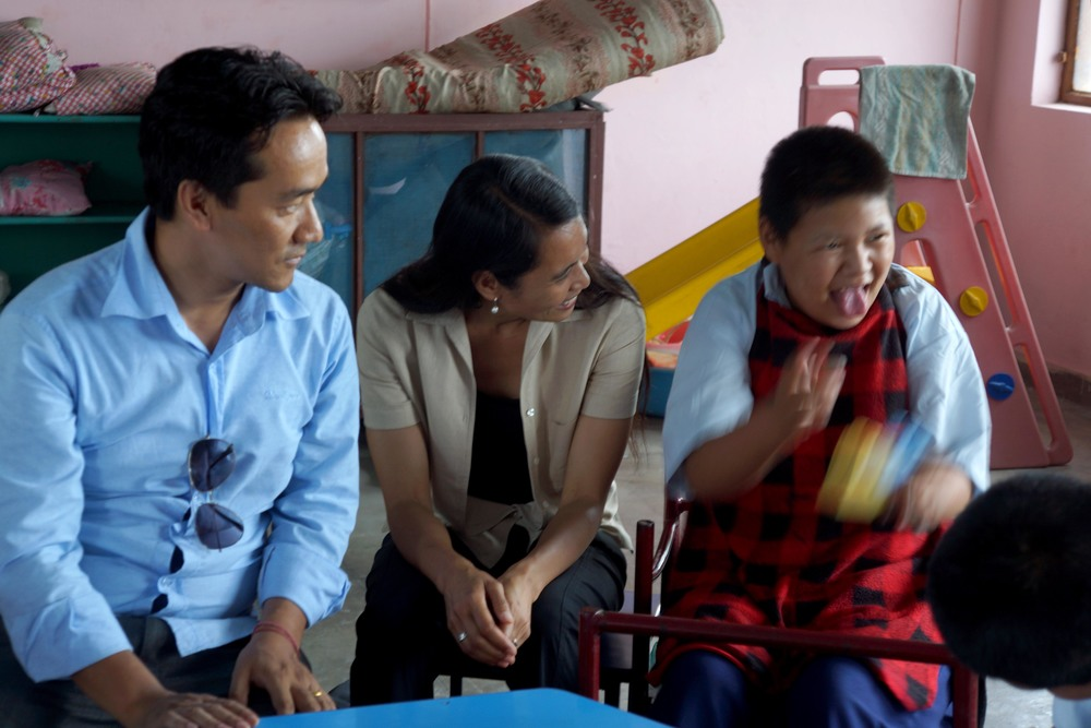 An adult (left) and Ana Rowena McCullough (center) laughing as a Tibetan child sticks their tongue out (right)