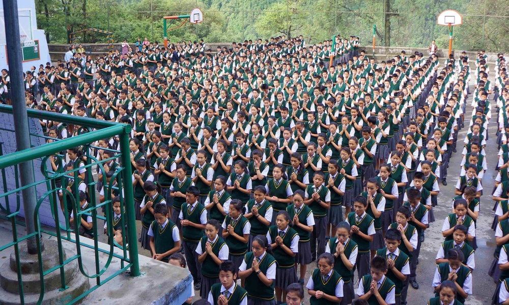 Picture of a group of Tibetan schoolchildren in uniform sitting in organized rows.