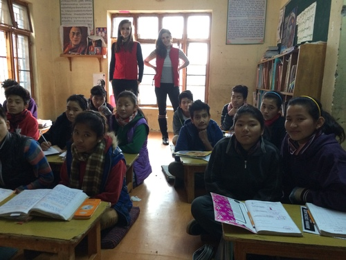 Image of Tibetan schoolchildren sitting in rows, with Maia Mosse (center left, background) and Diana Saville (center, background) standing in the back