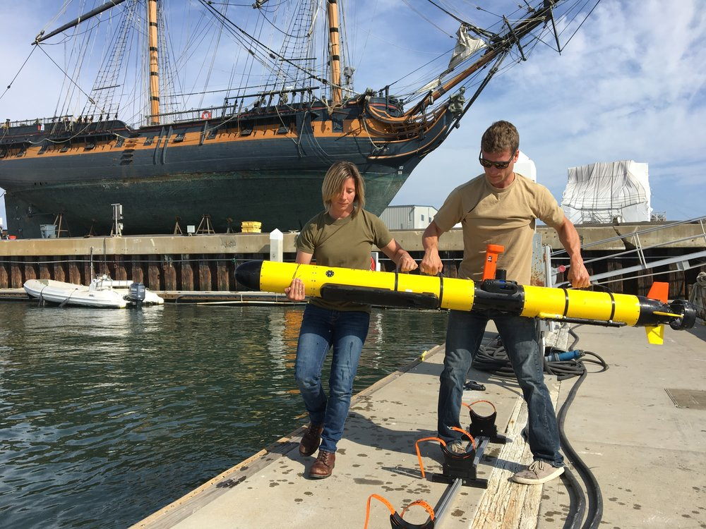 Orca Maritime employees Kimberly Flax and Chestley Howell with San Diego's HMS Surprise in the background