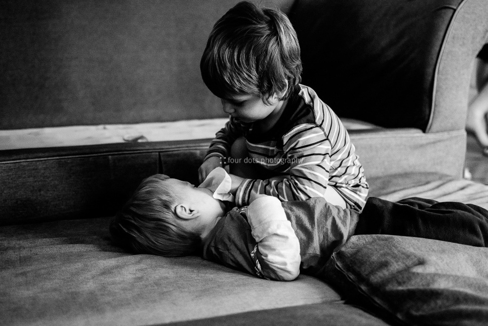 love is offering to wipe little brother's nose for him.