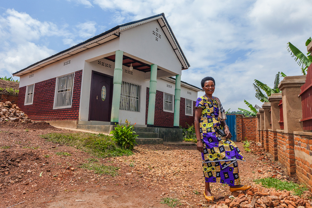 Maria Bedabazingwa shows off her new home. With her earnings from selling coffee, she was able to build a house, and purchase a cow and health insurance.