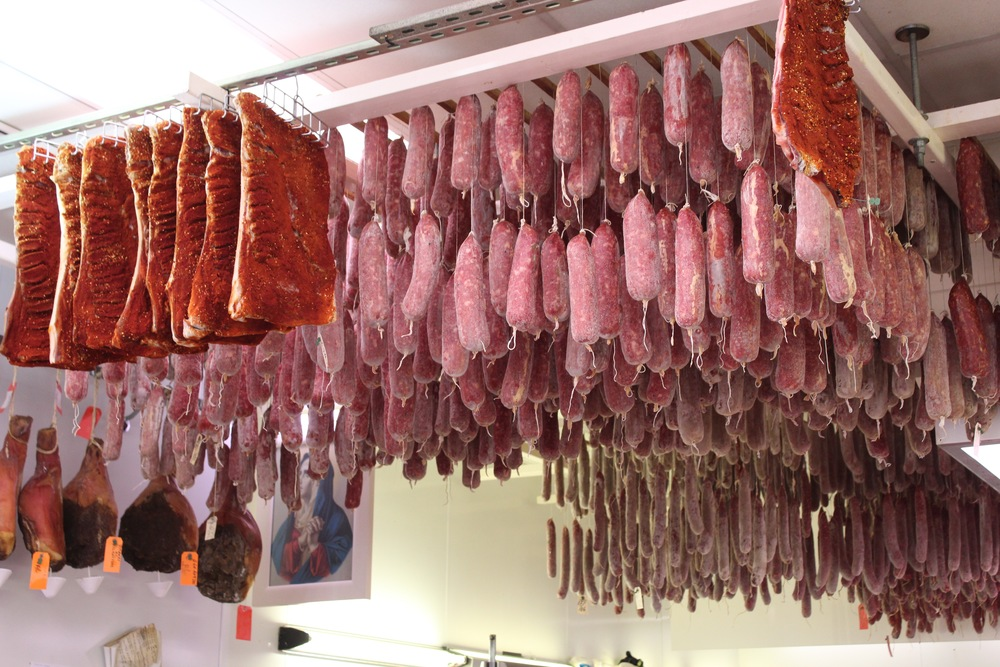 Soppressata curing at Biancardi's next to a painting of the Virgin Mary