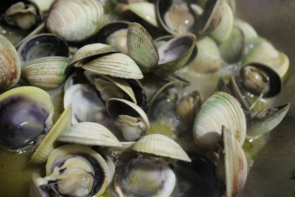 Vongole or tiny Manilla clams opening up in a large sauté pan. When the pasta is almost cooked, use tongs to transfer it directly to the pan so that it will finish cooking in the clam juice and absorb the extra flavor.